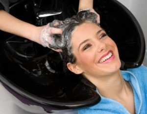 hair stylist washing woman hair with shampoo